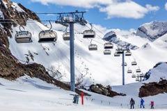 Skieurs se tenant sur la pente de ski de cirque de montagne au jour ensoleillé sur le fond d'hiver d'ascenseur de benne suspendue Photos stock