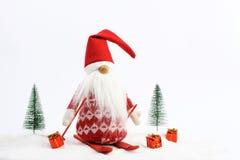 Skifahren des Weihnachtshelfers (Elfe) auf Schnee als Nächstes zwei schneebedeckte Bäume und drei Geschenk- rot und weißefarben Stockfoto