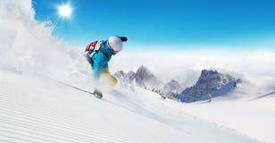 Skifahrer auf dem Piste, der abwärts läuft stockbild
