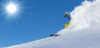 Skifahrer auf dem Piste, der abwärts läuft stockfotos