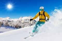 Skifahrer auf dem Piste, der abwärts läuft stockbilder
