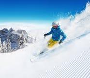 Skifahrer auf dem Piste, der abwärts läuft stockfoto