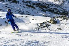 Skifahrer auf schneebedecktem Steigung Felskinn-Schnee trägt Wege zur Schau Stockfotografie