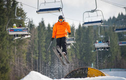 Skifahrer, der über eine Hürde am Wintertag fliegt stockfotografie