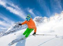 Skifahrer, der abwärts im Hochgebirge Ski fährt lizenzfreie stockbilder