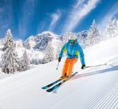Skifahrer, der abwärts im Hochgebirge Ski fährt stockfotografie