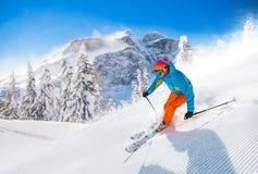 Skifahrer, der abwärts im Hochgebirge Ski fährt lizenzfreie stockfotos