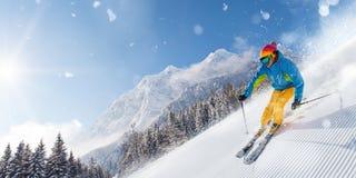 Skifahrer, der abwärts im Hochgebirge Ski fährt stockfotos