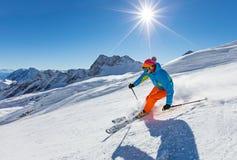 Skifahrer, der abwärts im Hochgebirge Ski fährt lizenzfreie stockfotografie