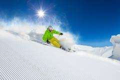 Skifahrer, der abwärts im Hochgebirge Ski fährt stockfoto