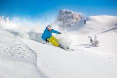 Skifahrer, der abwärts im Hochgebirge Ski fährt Stockbilder