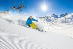 Skifahrer, der abwärts im Hochgebirge Ski fährt lizenzfreies stockbild