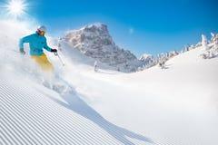 Skifahrer, der abwärts im Hochgebirge Ski fährt stockbild