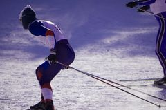 Skifahrer, der abwärts während des sonnigen Tages im Hochgebirge Ski fährt lizenzfreie stockfotografie