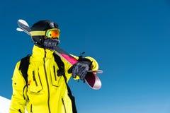 Skifahrer, der auf einer Steigung steht Mann in einer hellen Klage, im Sturzhelm und in der Maske im Skifahren soll Ski fahren Im Stockfotografie