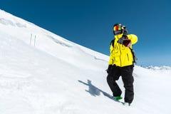 Skifahrer, der auf einer Steigung steht Mann in einer hellen Klage, im Sturzhelm und in der Maske im Skifahren soll Ski fahren Im Lizenzfreies Stockbild