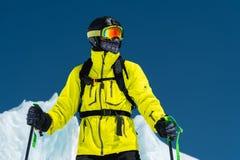 Skifahrer, der auf einer Steigung steht Mann in einer hellen Klage, im Sturzhelm und in der Maske im Skifahren soll Ski fahren Im Stockbild