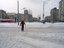 Skifahrer, der die Straße in der Stadt kreuzt Ski fahren in der Stadt Kiew lizenzfreies stockbild