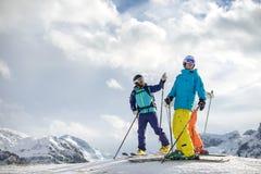 Skifahrer, der Freunden die Gebirgsoberteile zeigt Stockfotos