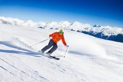 Skifahrer in der Maske schiebt schnell beim Ski fahren von der Steigung Lizenzfreies Stockfoto