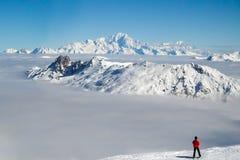Skifahrer, der Mont Blanc über einem Wolkenmeer betrachtet Stockbild