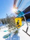 Skifahrer, der am Skiaufzug im Hochgebirge während des sonnigen Tages sitzt Lizenzfreie Stockbilder