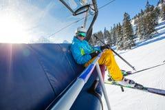 Skifahrer, der an der Skisesselbahn sitzt lizenzfreies stockbild