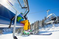 Skifahrer, der an der Skisesselbahn sitzt lizenzfreie stockfotografie