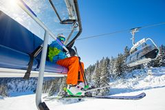 Skifahrer, der an der Skisesselbahn sitzt stockbilder