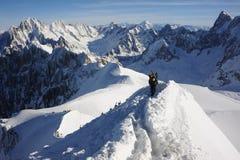 Skifahrer, die auf den Gebirgsrücken bedeckt mit Schnee in den französischen Alpen im Winter mit schönem Panorama und blauem Himm Lizenzfreie Stockbilder