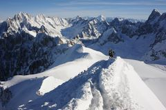 Skifahrer, die auf den Gebirgsrücken bedeckt mit Schnee in den französischen Alpen im Winter mit schönem Panorama und blauem Himm Stockbilder