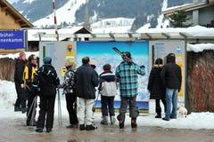 Skifahrer, die den Vorstand mit Skisteigungen überprüfen Stockfoto