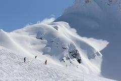 Skifahrer, die die Steigung am Skiort hinuntergehen Lizenzfreie Stockfotos