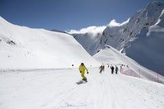 Skifahrer, die die Steigung am Skiort hinuntergehen Stockbild