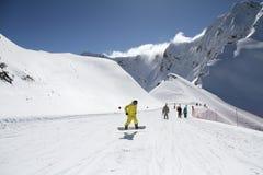 Skifahrer, die die Steigung am Skiort hinuntergehen Stockfotos