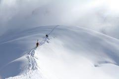 Skifahrer, die einen schneebedeckten Berg klettern Stockfotografie