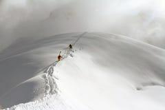 Skifahrer, die einen schneebedeckten Berg klettern Lizenzfreie Stockfotos