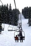 Skifahrer, die herauf einen Stuhl-Aufzug reiten Stockfotos