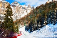 Skifahrer, die hinunter die Steigung im Skiort in den Dolomiten Ski fahren stockfotos
