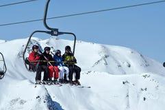 Skifahrer, die mit einem Skiaufzug in einem Skiort steigen Lizenzfreies Stockbild