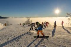 Skifahrer, die Sonnenaufgang in den Bergen genießen Lizenzfreie Stockbilder