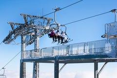 Skifahrer, die zur hohen Bergstation auf dem Skiaufzug ankommen Stockfotos