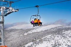 Skifahrer, die zur hohen Bergstation auf dem Skiaufzug ankommen Lizenzfreie Stockfotos