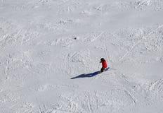 Skifahrer in einer roten Klage beim Abstieg auf der Skisteigung Lizenzfreies Stockfoto