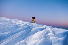 Skifahrer gehen Berg hinauf Stockfotografie