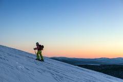 Skifahrer gehen Berg hinauf Lizenzfreie Stockfotos