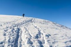 Skifahrer geht oben zur Spitze Stockbilder