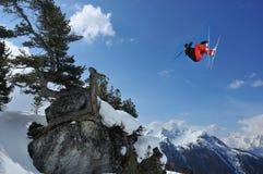 Skifahrer im Rot und im Schwarzen führt Hochsprung durch Lizenzfreie Stockfotos