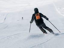 Skifahrer im schwarzen Abfahrtskilauf auf einer Skisteigung Ansicht von der Rückseite Lizenzfreies Stockbild