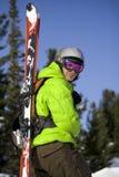 Skifahrer mit Skis auf der Rückseite Stockfotografie